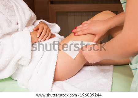 woman at cosmetics salon waxing legs - stock photo