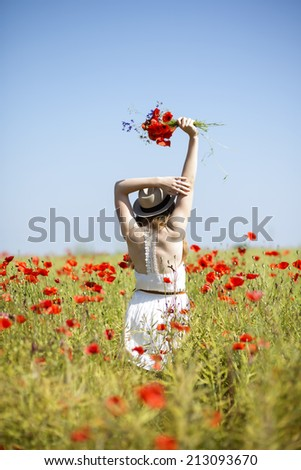 Woman at dress and hat with poppy bouquet - stock photo