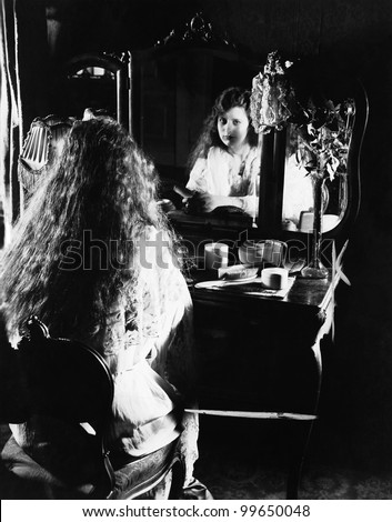 Woman at dressing table looking in mirror - stock photo