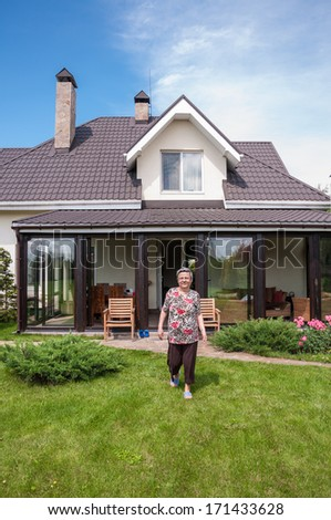 woman at garden of her private house - stock photo