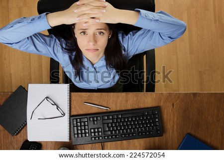 woman at her desk feeling the stress of work, taken from a birds eye view - stock photo