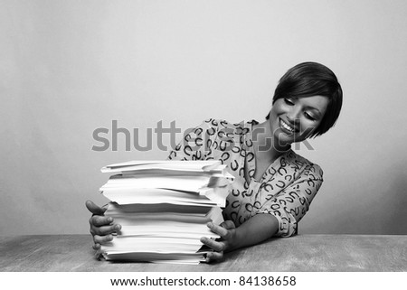 woman at her desk with lots of paper work to do - stock photo