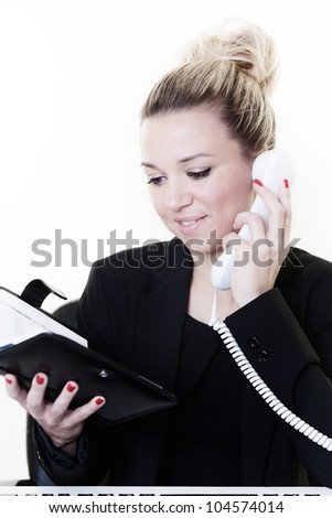 woman at her desk working checking her filofax making sure she's not got any meetings today - stock photo