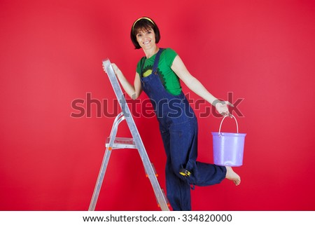 Woman at her house next to a red wall - stock photo