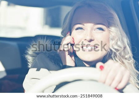woman at her mobile telephone while she's drriving her car and smiles - stock photo