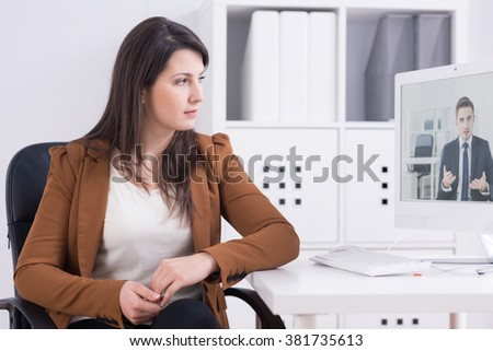 Woman at her office in front of computer talking with man in suit via skype