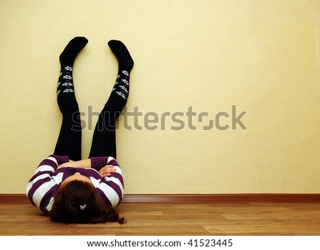 Woman at home in domestic clothes laying on the floor - stock photo