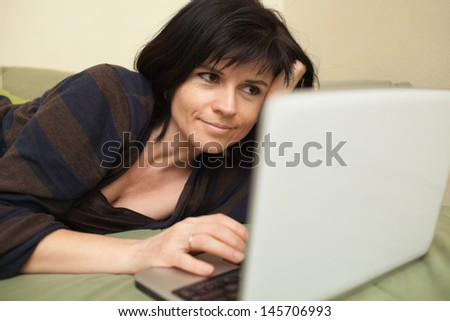 Woman at home lying on sofa and working with laptop