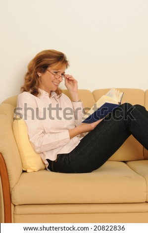 woman at home, reading in a book.