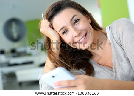 Woman at home relaxing and using smartphone