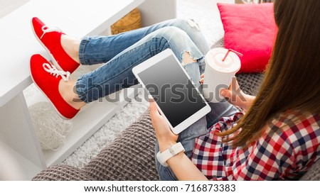 Woman at home relaxing on sofa couch reading email on the tablet computer wifi connection