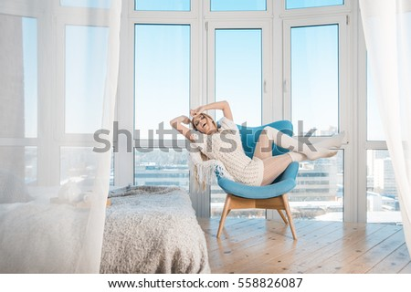 woman at home sitting on modern chair in front of window relaxing in her living room, stretching with closed eyes. Blondy girl enjoy inside bedroom interior near cozy bed with teapot. White curtains.