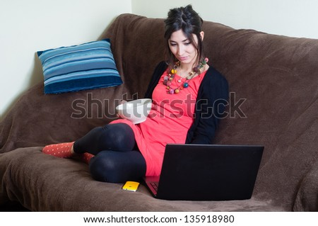 woman at home using notebook on couch