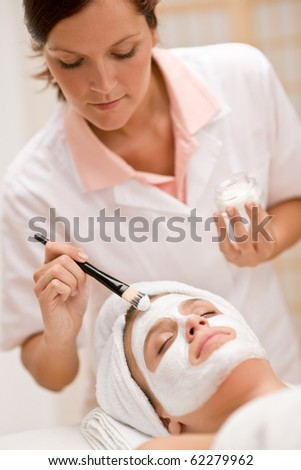 Woman at luxury spa beauty treatment getting facial mask