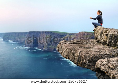 Woman at meditation on the edge of cliff