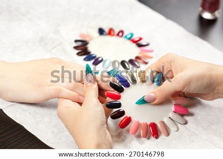 Woman at nail studio chosing color of nail polish