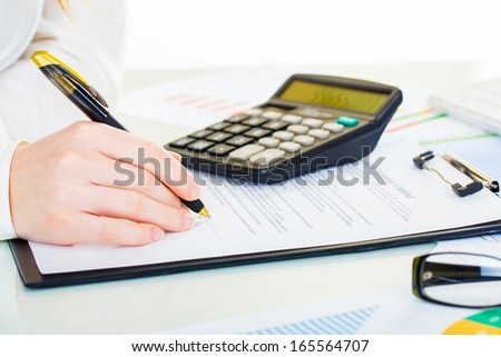 Woman at office desk signing a contract with shallow focus on signature.