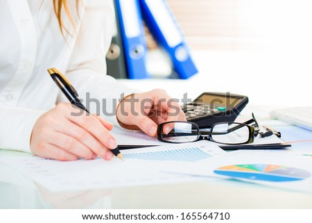 Woman at office desk signing a contract with shallow focus on signature. - stock photo