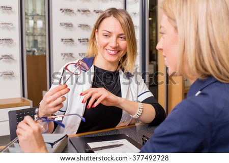 Woman at optometry shop choosing glasses
