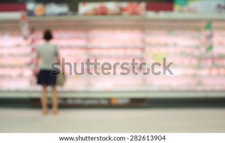 woman at shelves with meat in a large supermarket blurred background - stock photo