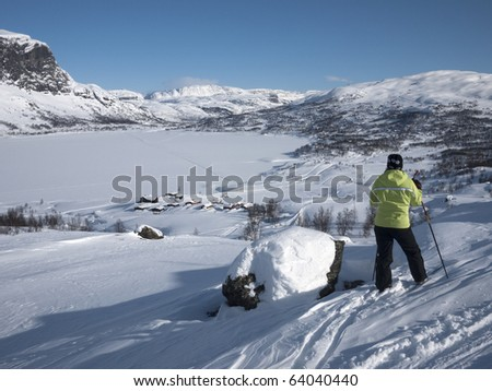 Woman at ski resting alongside a stone having a panoramic peaceful view towards a snow covered lake with mountain summits in the background at winter time in norway