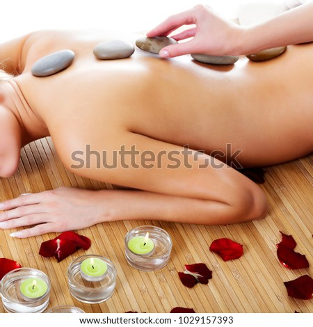Woman at spa center, naked female back with hot stones on it