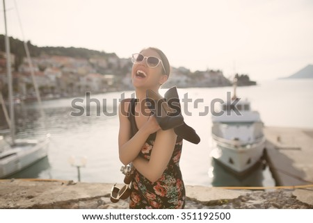 Woman at summer festival holding high heels.Young European brunette jumping,ready to party.Happy young woman on vacation dancing at the beach on beautiful summer sunset - stock photo