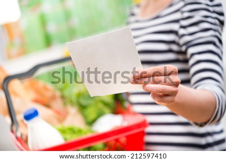 Woman at supermarket holding a full shopping basket and a shopping list. - stock photo