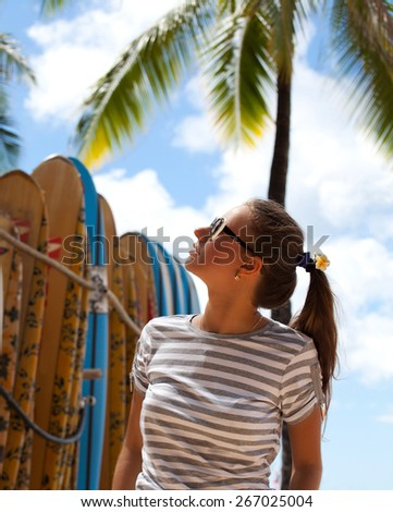 Woman at surfboard rental surf shop, looking and walking next to rack of many surf boards to rent for surf class on famous Waikiki beach, Honolulu City, Oahu, Hawaii, USA. - stock photo