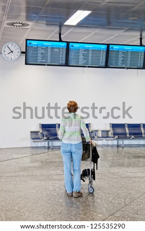 woman at the airport attentively looks at an information display