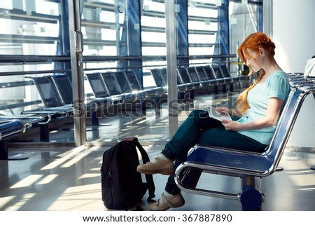 woman at the airport. redhead girl with tablet computer. business and travel - stock photo
