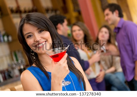 Woman at the bar having a drink and looking happy - stock photo