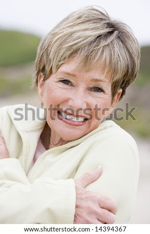 Woman at the beach cold and smiling - stock photo