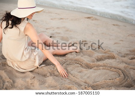 Woman at the beach drawing heart on a sand