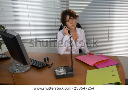 Woman at the desk on the phone - stock photo