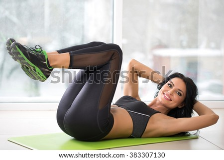 woman at the gym doing exercise on the floor - stock photo