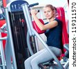 Woman at the gym exercising on a machine. Arm exercise - stock photo