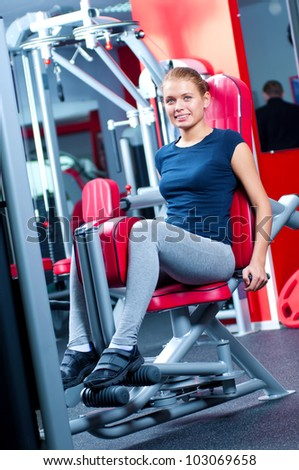 Woman at the gym exercising on a machine. Legs and buttocks