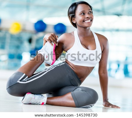 Woman at the gym stretching her leg before workout - stock photo