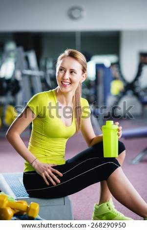 Woman at the gym with a bottle - stock photo