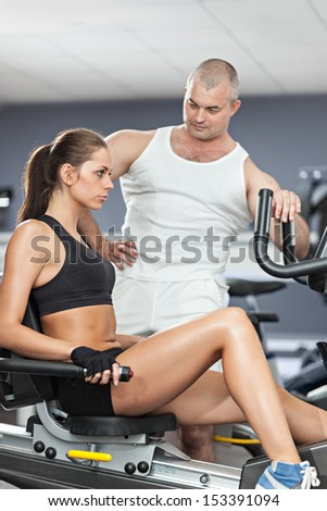 Woman at the health club with her personal trainer, learning the correct form on the cycling machine. - stock photo