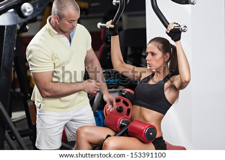 Woman at the health club with her personal trainer, learning the correct form on the pulldown machine. - stock photo