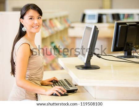 Woman at the library searching for a book on computer - stock photo