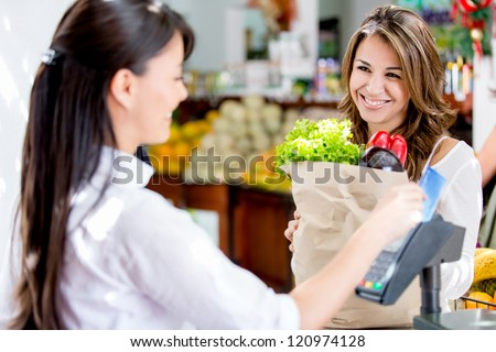 Woman at the local market's checkout paying by debit card - stock photo