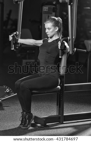 Woman at the sport gym doing arms exercises on a machine. Black and white sport club.