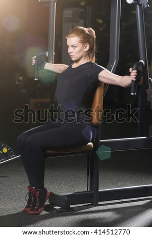 Woman at the sport gym doing arms exercises on a machine. Dark sport club. - stock photo