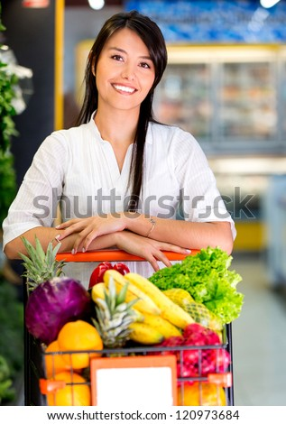 Woman at the supermarket with a shopping cart full of groceries - stock photo