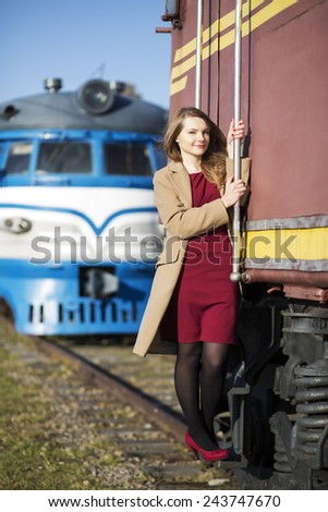 Woman at  train wagon stairs hold on boundary - stock photo