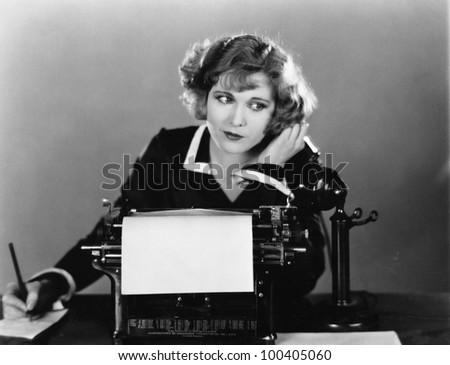 Woman at typewriter on telephone - stock photo