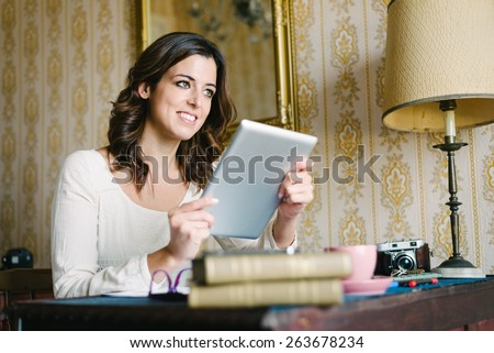 Woman at vintage looking home working and reading on digital tablet. Female young worker or student doing her job in retro desk. Vintage filtered image. - stock photo